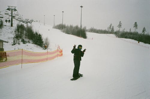 Full body anonymous snowboarder in warm clothes standing on snowboard on snowy mountain slope and showing two fingers gesture while spending weekend in ski resort