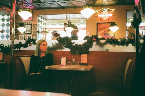 Young female relaxing at table of modern cafe with Christmas decorations and glowing lamps
