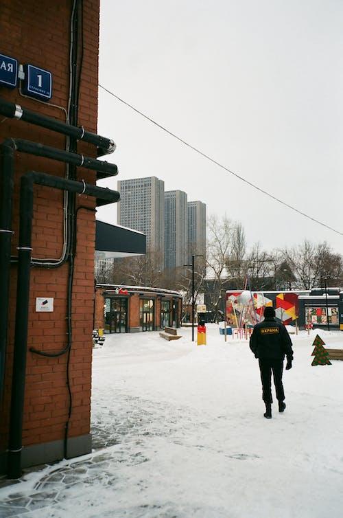 Man in outerwear walking in snowy town with modern buildings
