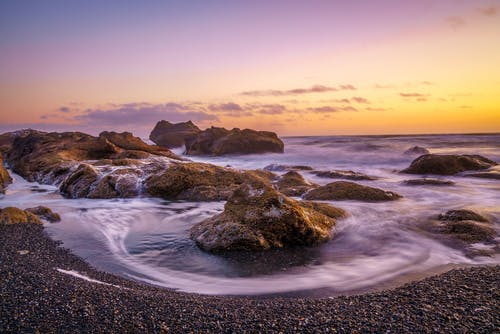 Brown Rock Formation on Sea Shore during Sunset