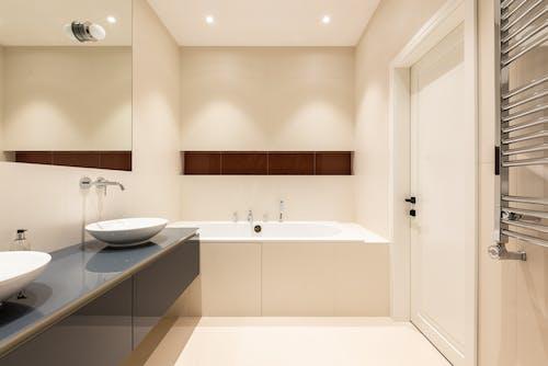 Bathroom interior with bath near sinks on counter near mirror