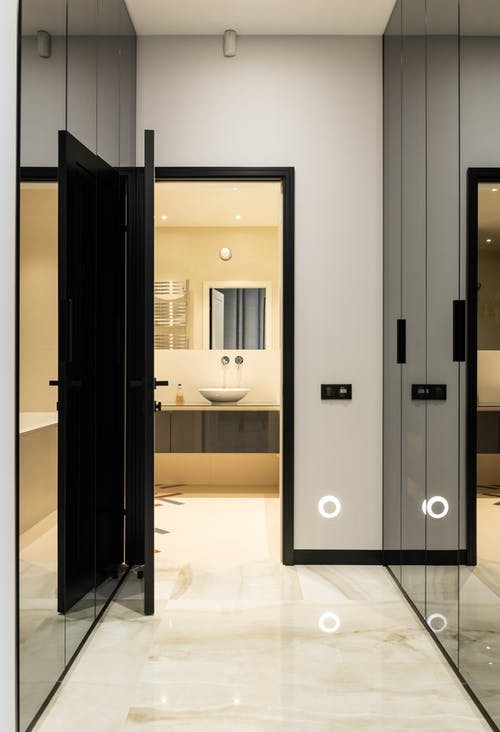 Interior of modern house with big glass cabinets near door to bathroom with sink on counter