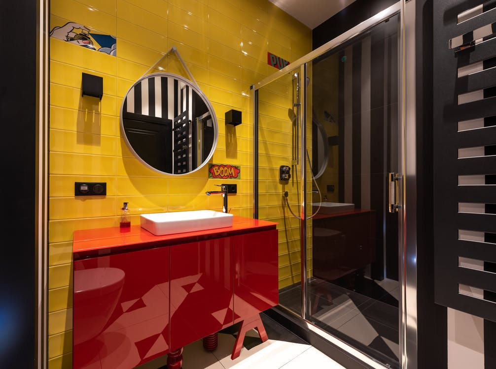 Colorful bathroom with sink on cabinet near mirror and shower