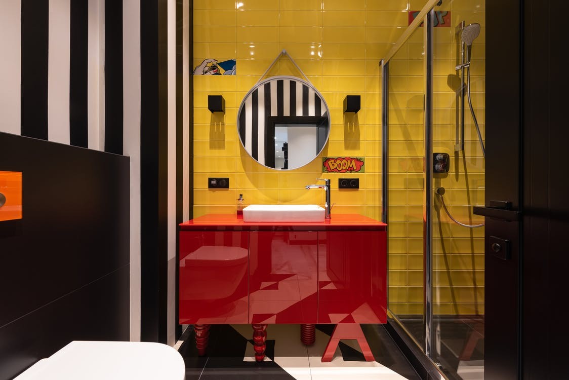 Interior of modern bathroom with sink on red cabinet near tap and mirror hanging on yellow wall near toilet and shower