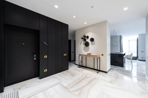 Interior of modern light hall with black doorway and stylish table at wall with entrance to open plan kitchen with black island conuter