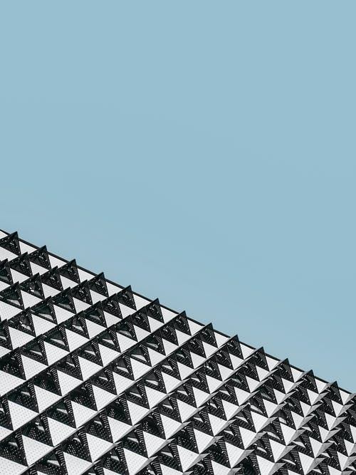 From below view of contemporary geometric building in daytime with clear blue sky on background
