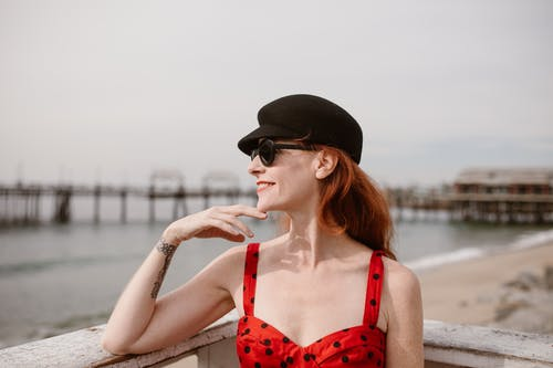 Happy adult female tourist with long red hair in elegant dress and sunglasses touching chin and smiling while admiring sea from terrace on sunny day