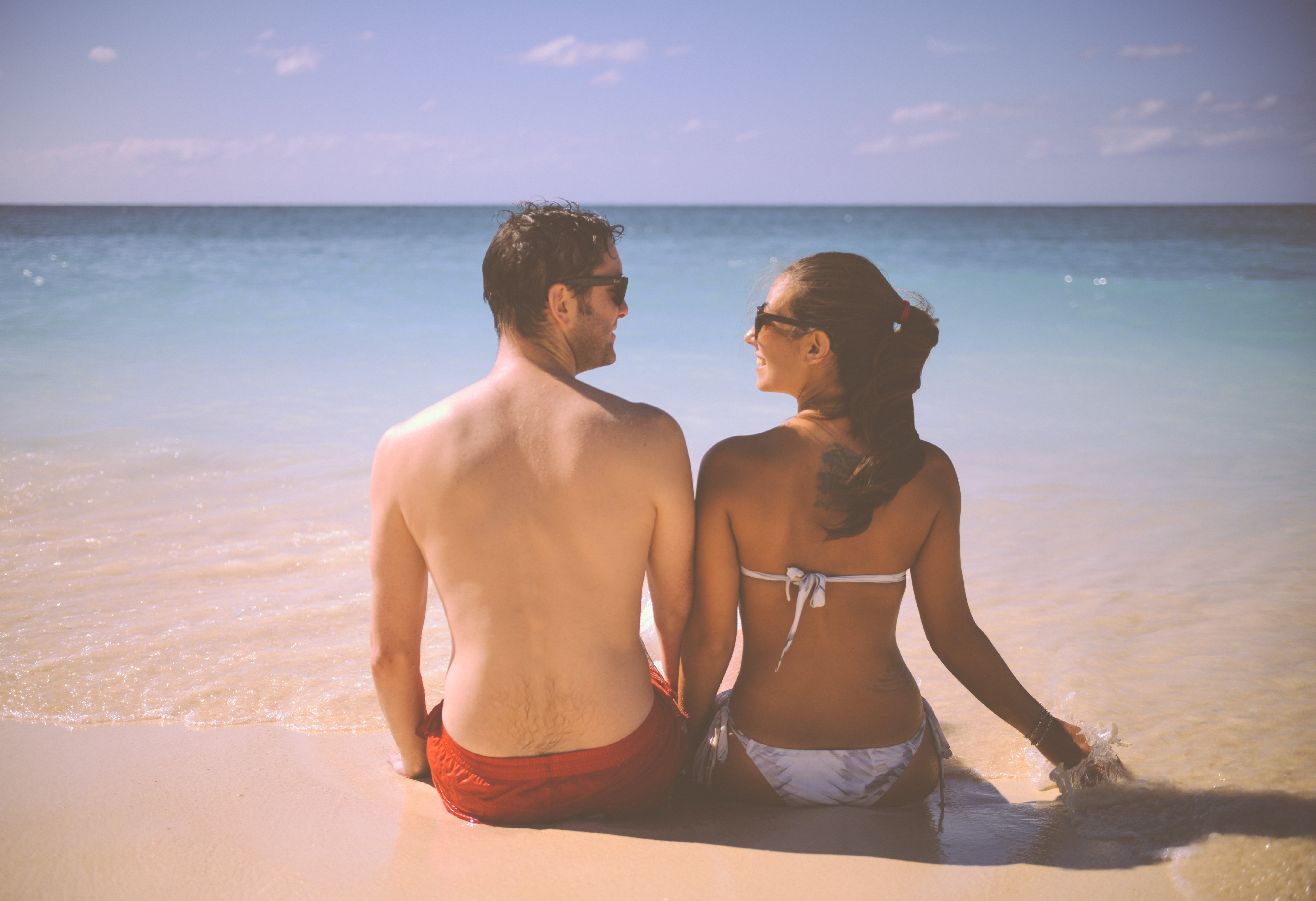 Man and Woman Sitting Beside Body of Water