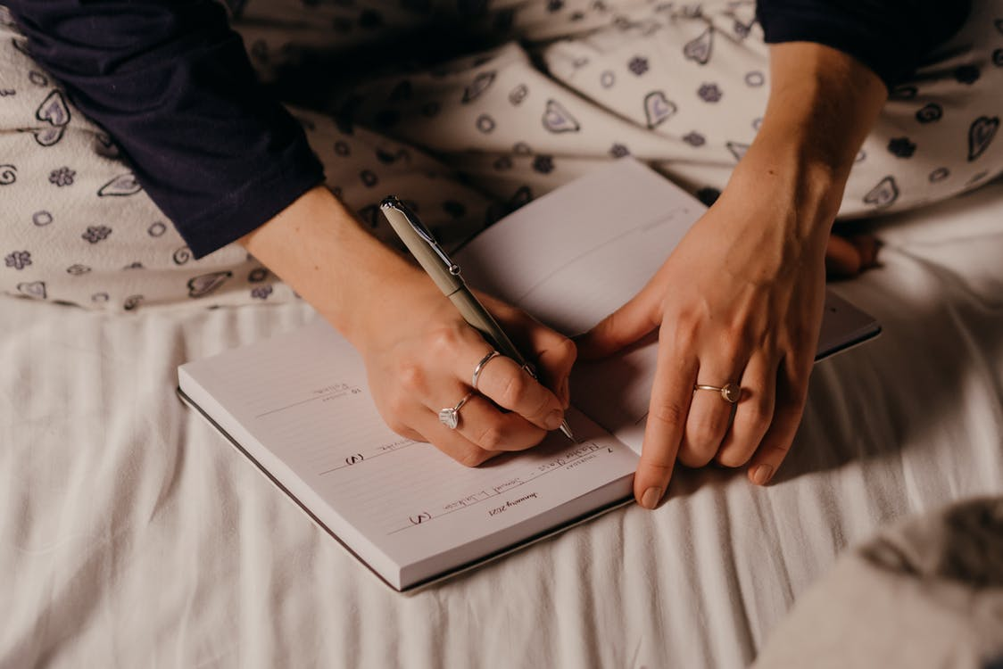A Person Writing on a Journal