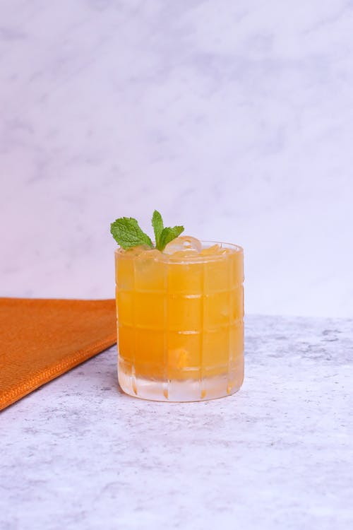 Transparent glass of tasty citrus drink with fresh mint leaves and ice on marble surface