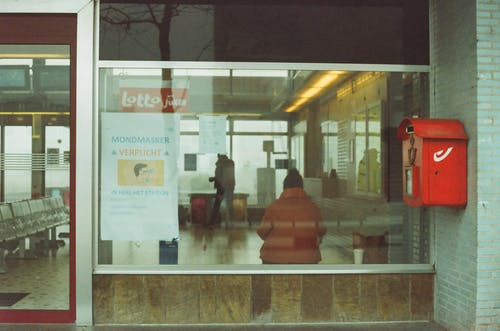 Through glass of anonymous tourists in warm outerwear standing in waiting room of modern railway station