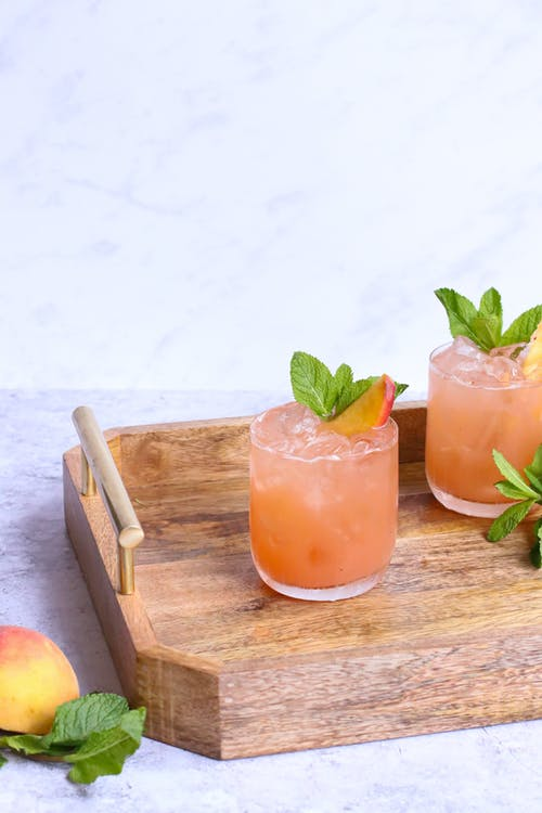 Glasses of tasty alcoholic drinks decorated with fresh peach slices and mint leaves on wooden tray