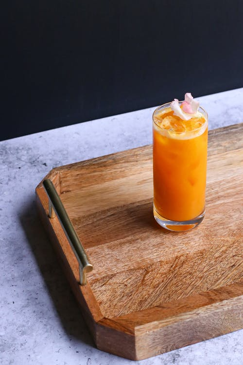 From above of tasty refreshing drink with citrus juice and flower on ice on wooden tray