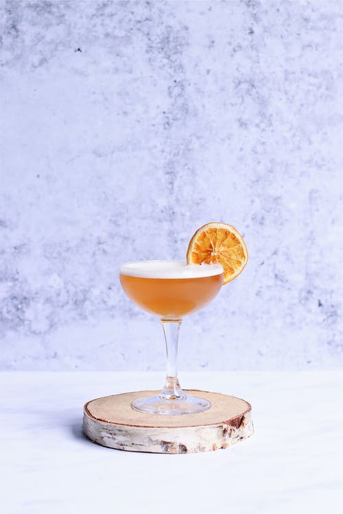 Glass of delicious alcoholic drink with foam decorated with citrus fruit slice on wooden stand on light background