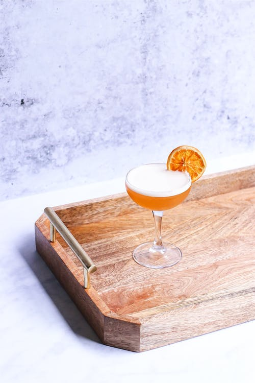 From above of delicious alcoholic beverage with orange slice on glass on wooden tray