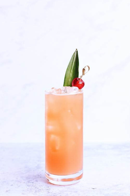 Glass of refreshing berry drink in light studio