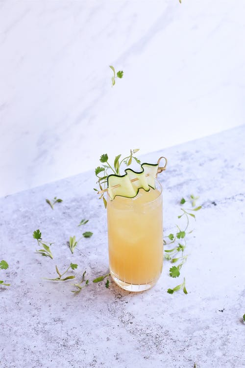 Glass of sour ginger cocktail on marble table