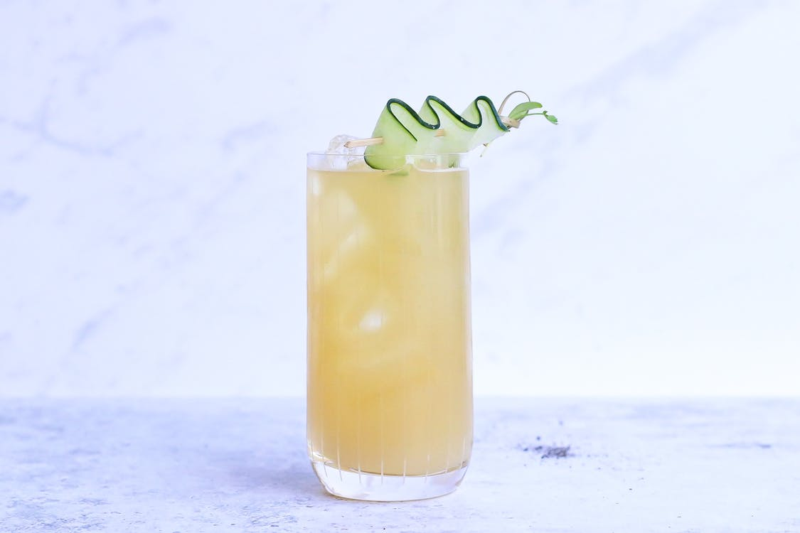 Glass of yummy sour ginger lemonade garnished with cucumber slice and served on light marble table in studio