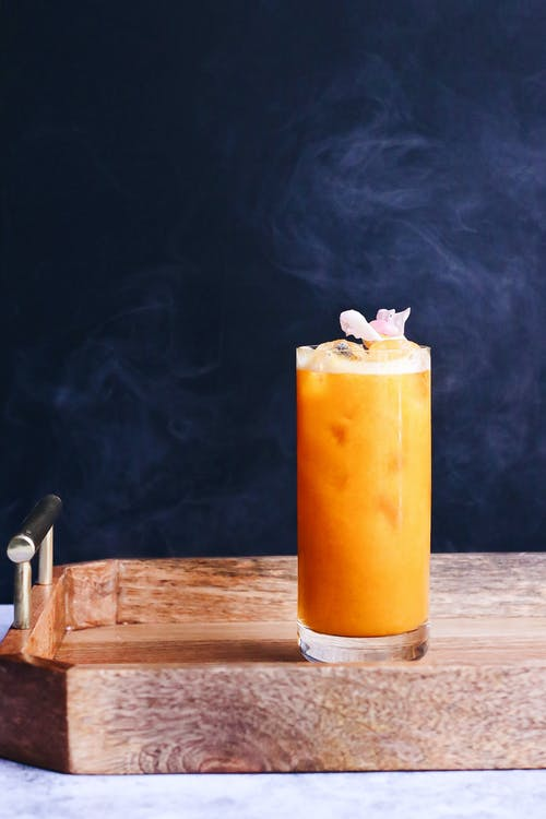 Sweet cold orange beverage with ice served on wooden tray in light kitchen