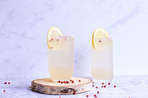 Glasses of delicious cold lemonade decorated with lemon slice and berries on wooden board in light studio