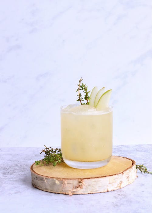 Glass of sweet cold cocktail garnished with pear slices