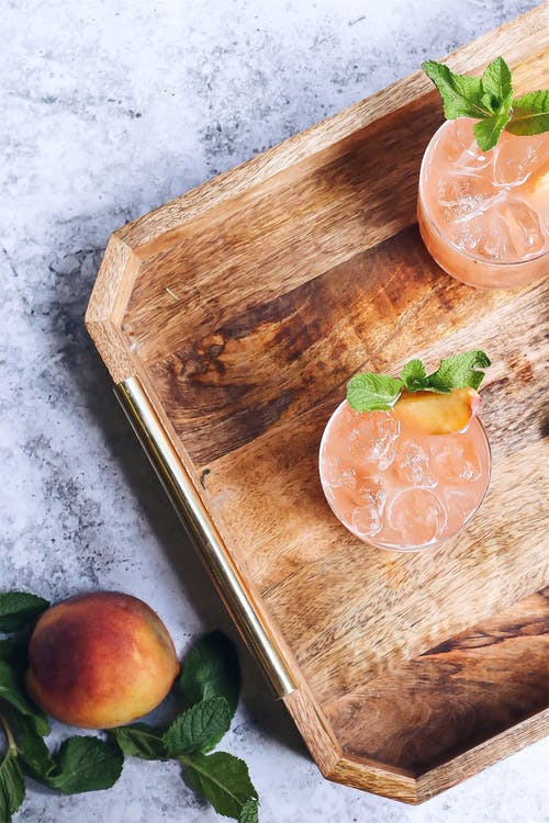 Top view arrangement of delicious icy berry drink decorated with mint and served on wooden tray near ripe peach