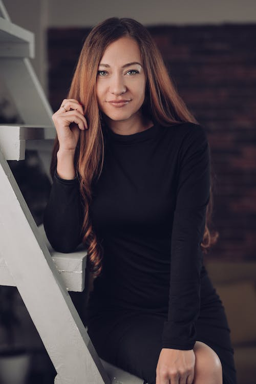 Smiling young woman in black dress with long hair looking at camera while sitting on ladder in house