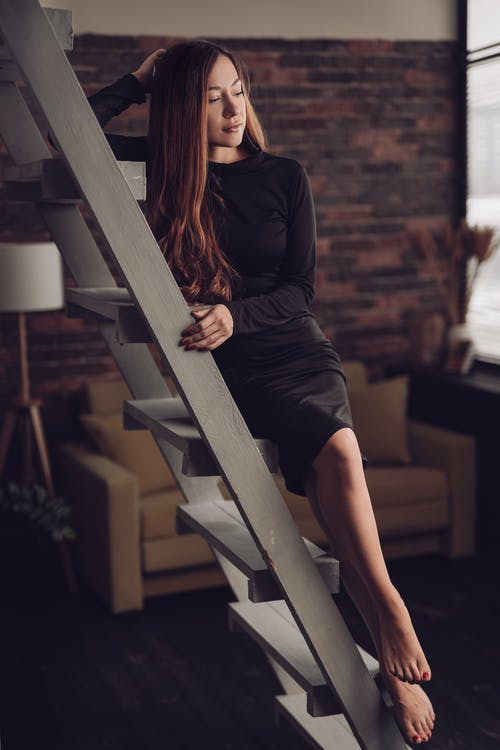 Young alluring female in black dress sitting with crossed legs on ladder while looking away in loft style house