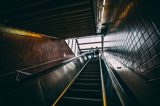 2 Person Standing on Black Escalator during Daytime