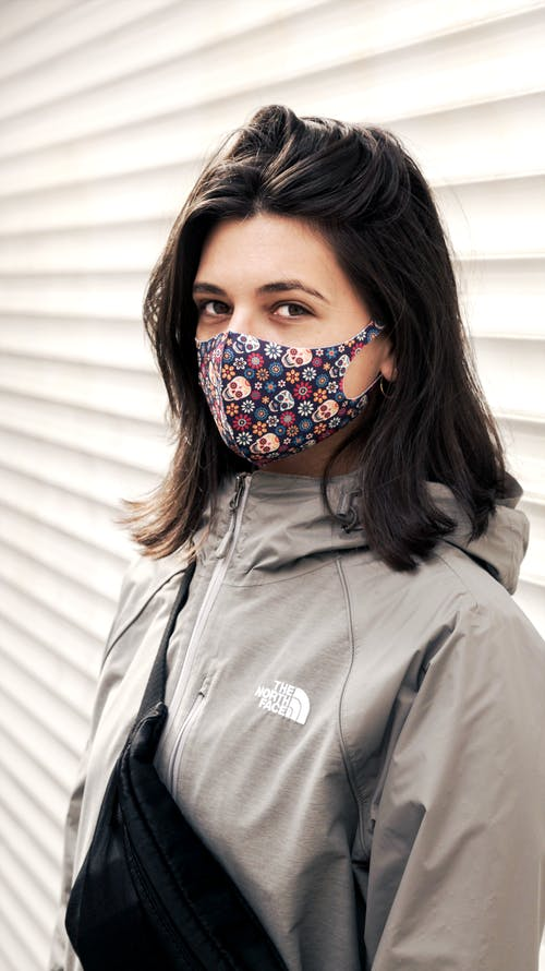 Woman in Gray Zip Up Jacket With Red and Black Floral Mask