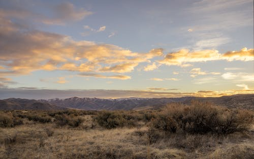 Scenic landscape of cloudy sunset sky over dry grassy terrain surrounded by hills in countryside