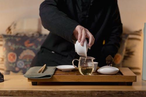 Person Pouring Tea on White Ceramic Mug