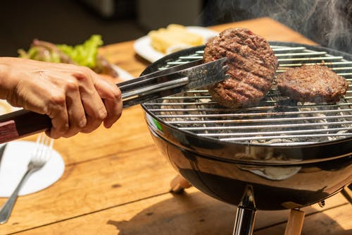 Person Holding Fork and Knife Slicing Meat