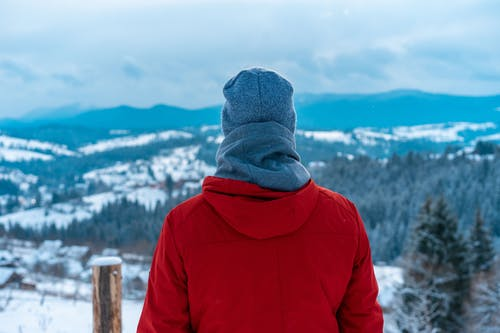 Person in Red Hoodie Wearing Gray Knit Cap Looking at Snow Covered Mountains