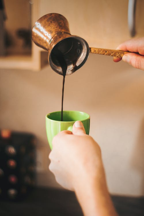 Crop person pouring coffee in cup