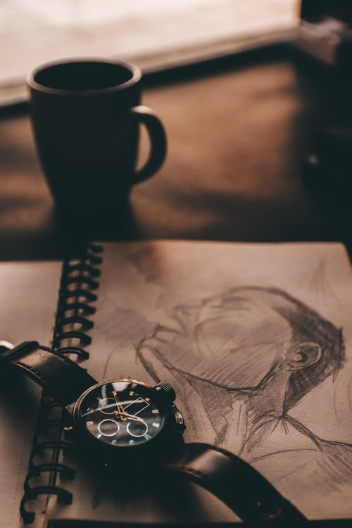 Table with wristwatch on sketchbook with drawing near coffee cup