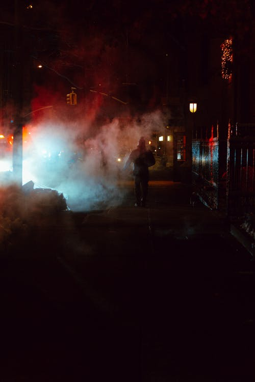 Murk street with walkway between residential building and road with steam and glowing lights of car at night time in city