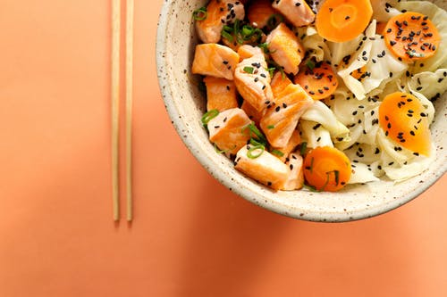 Top view of traditional Hawaiian poke bowl with salmon cabbage and carrot served with green onion and chia seeds on orange background