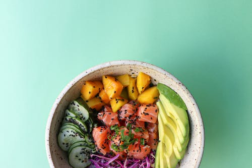 Top view of poke bowl consisting of chopped cucumbers avocado and salmon with mango and blue cabbage placed on green background