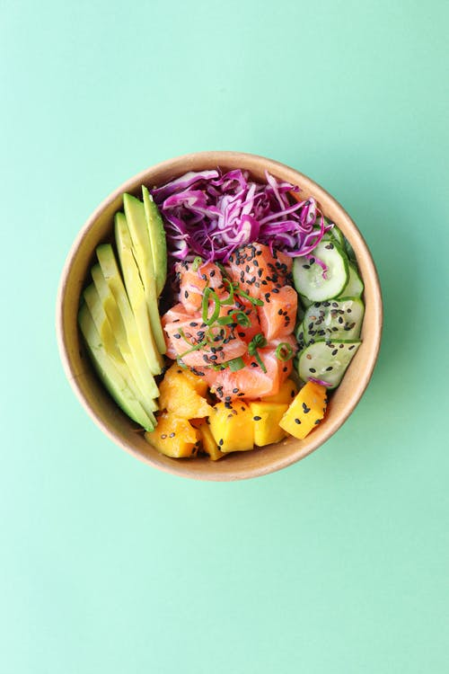 Bowl with delicious vegetables and diced raw fish