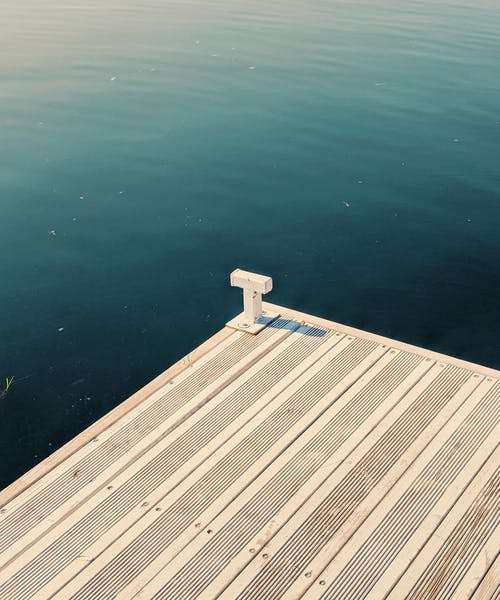 Wooden dock placed near calm water of calm sea in coastal terrain in bright sunlight in nature in summer day