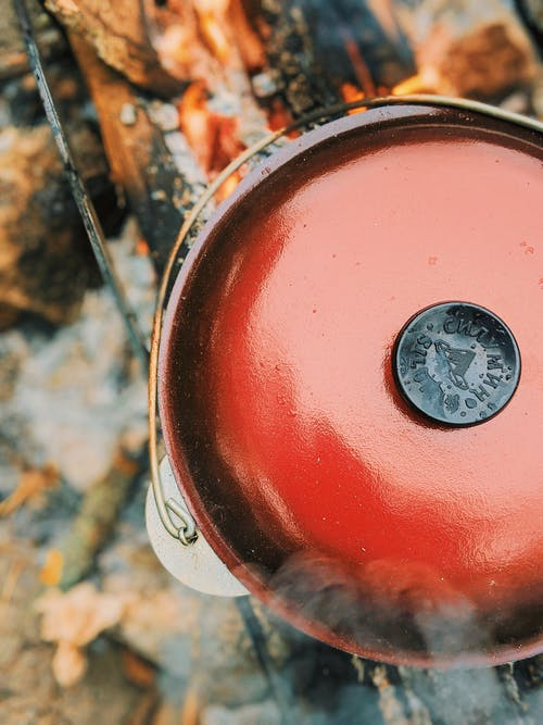 Top view of red metal pot with lid placed on burning firewood while cooking in nature on blurred background during camping