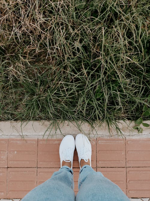 Photo of Legs in White Sneakers Near Grass