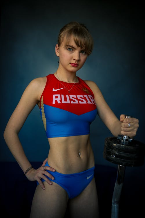 Woman in Red and Blue Sports Bra and Blue Shorts