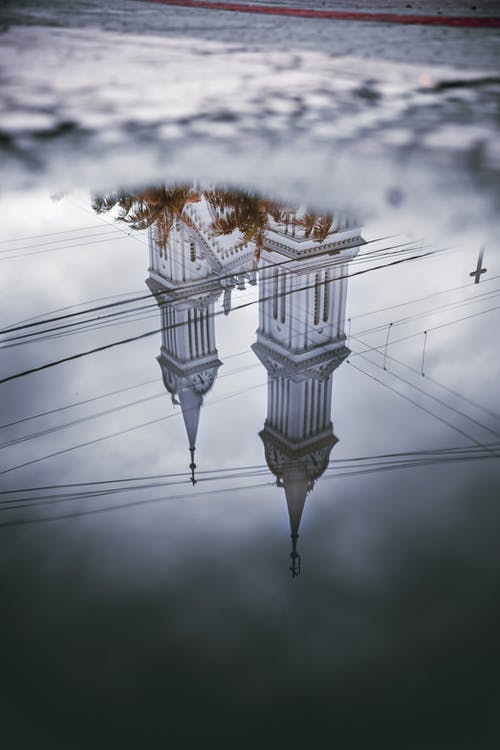 Reflection of old catholic cathedral in puddle on rainy day