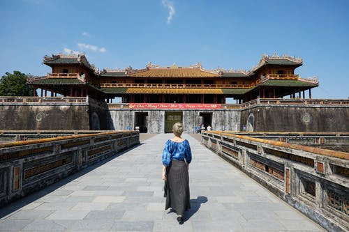 Full body back view of anonymous female traveler strolling on paved walkway near South Gate in Imperial City in Hue
