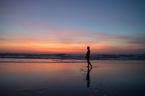 Silhouette of unrecognizable person walking on beach at sunset