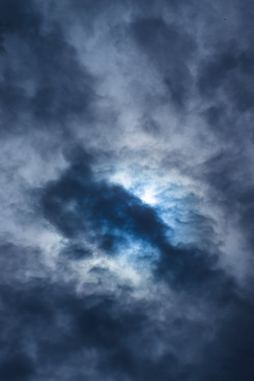 From below of fluffy dense gray cumulus clouds floating high in air on gloomy sky in nature in overcast weather