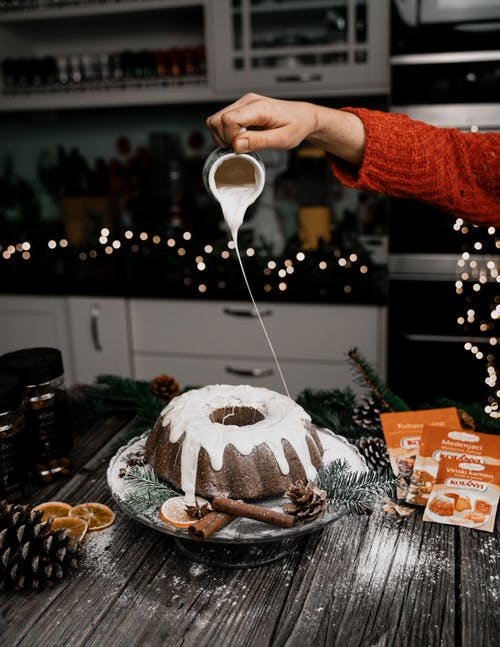 Person Pouring White Cream on Chocolate Cake