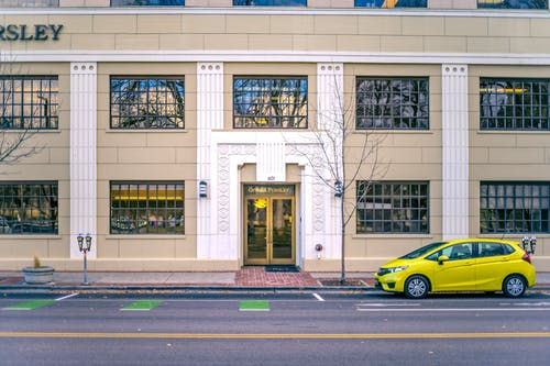 Yellow car parked near entrance of contemporary building